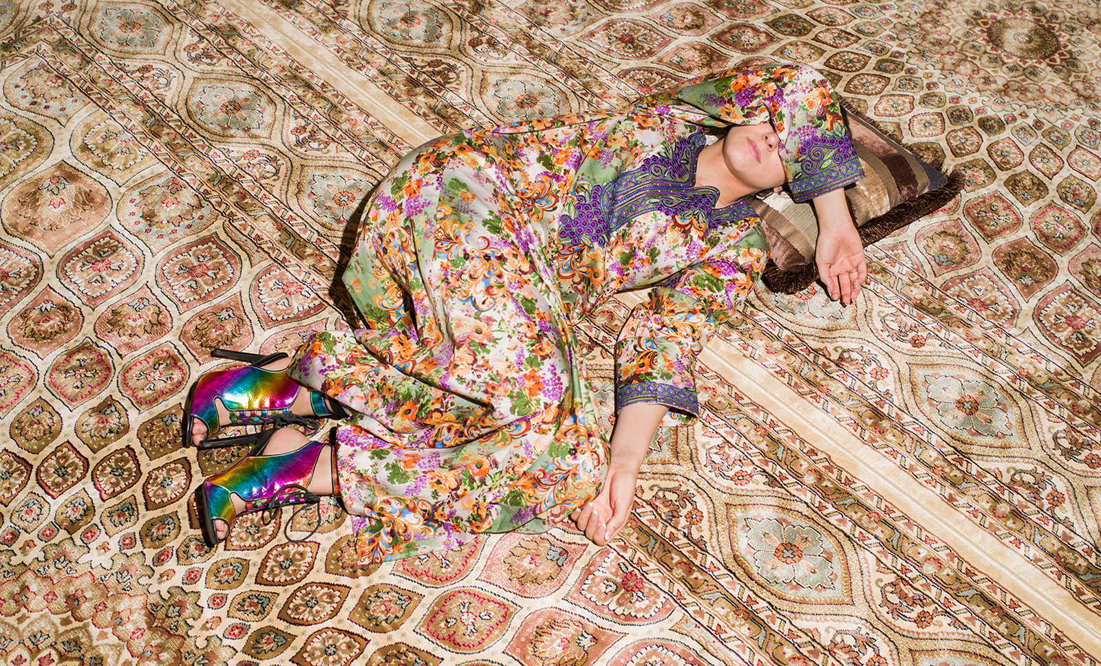 A woman in a floral print lays across a patterned rug, covering her face.