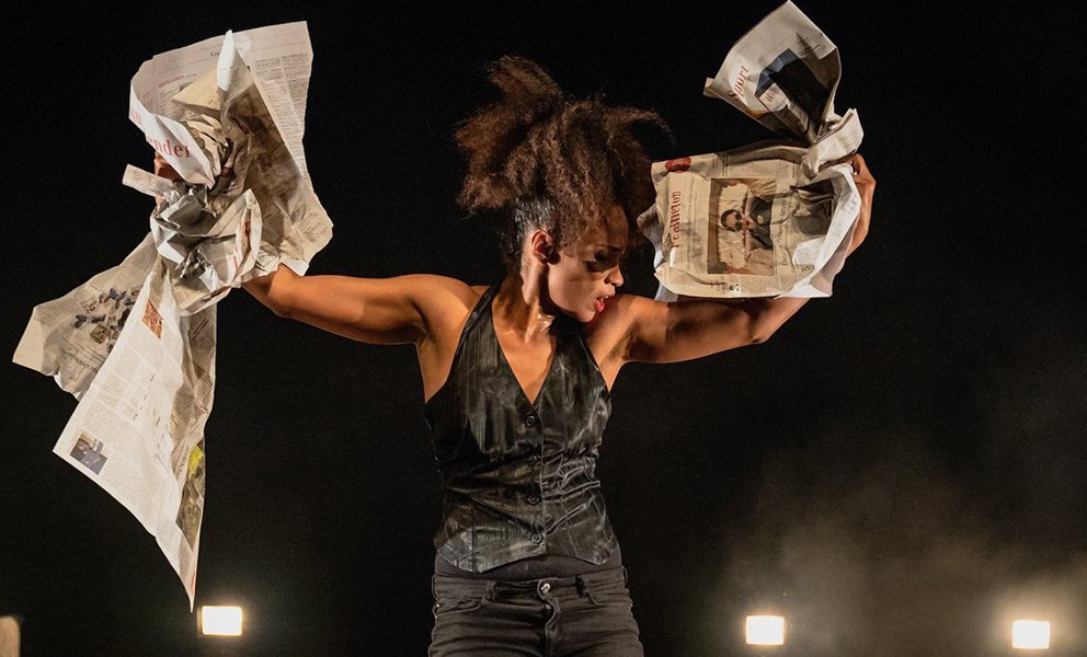 A Black female dancer, with her head turned to the right. Both arms are slightly raised and in her hands she clutches loose newspapers.