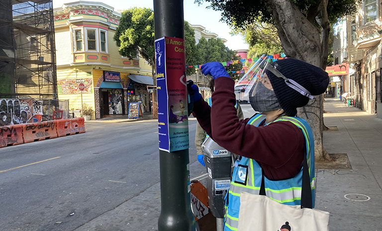 An Asian person wearing a face mask, face shield, black hat and blue safety vest is taping up infographic signs on a lightpole on a street.