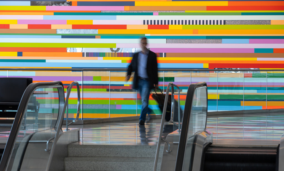 A man walking toward an escalator with a giant multi-colored mural behind him